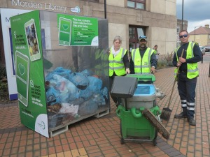 Councillor Judy Saunders with Mohamad Salim and Danny Jeeves, members of Merton Council's clean team, with the box of litter at midday