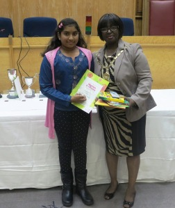 Mayor Councillor Akyigyina presents Sharaya Hareenthirakumar with the award for winner of the Best Drawing of a Garden by a Child category