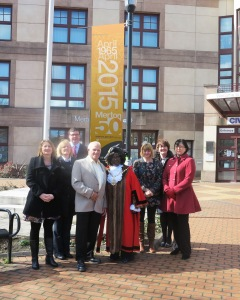 Mayor of Merton Councillor Agatha Akyigyina stands beside the new banners outside the civic centre to mark the occasion with Merton Council's longest serving member of staff Lew Block, who started working at the council in 1965, and staff who turn 50 years old this year