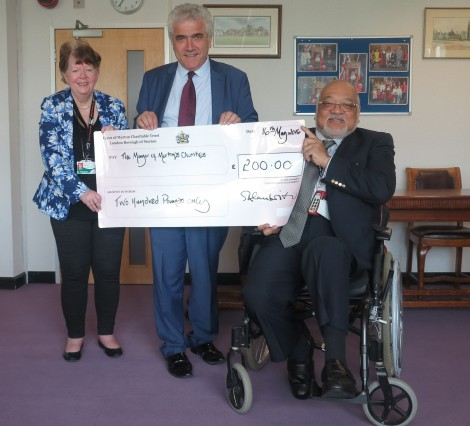 Leader of the council, Cllr Stephen Alambritis, presenting £200 pounds to former Mayor Cllr David Chung and former deputy mayor Cllr Pauline Cowper