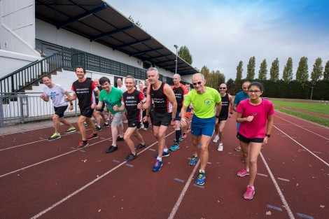 Cllr Nick Draper with the Wimbledon Windmilers at Wimbledon Park Athletics track with the renovated grandstand behind.